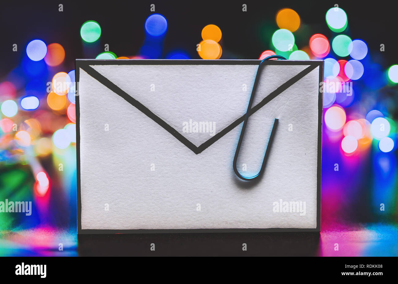 email with attachment clip and colorful fairy lights bokeh in the background shot at shallow depth of field - Stock Image