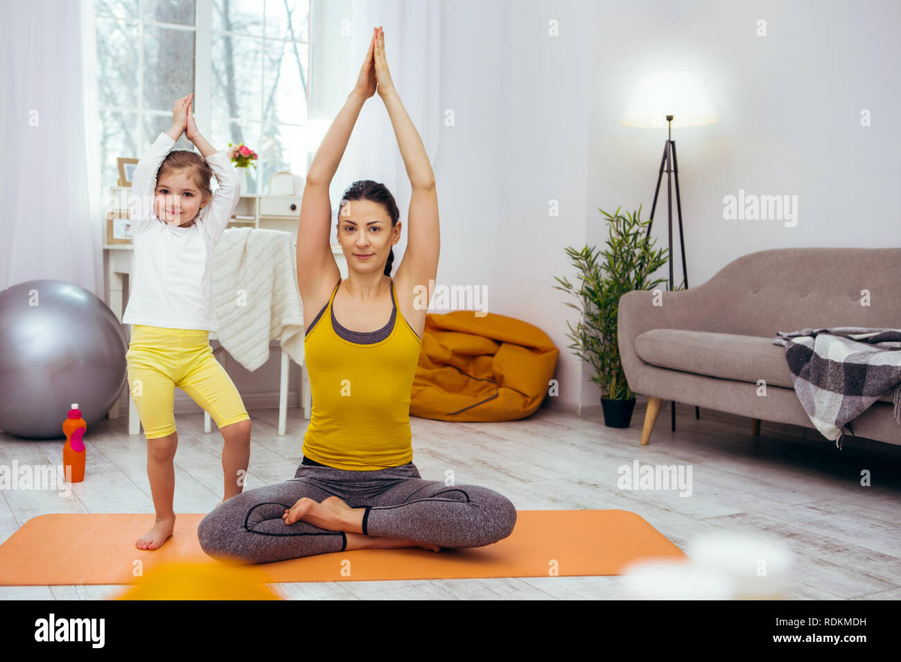 Nice delighted woman practicing yoga at home - Stock Image