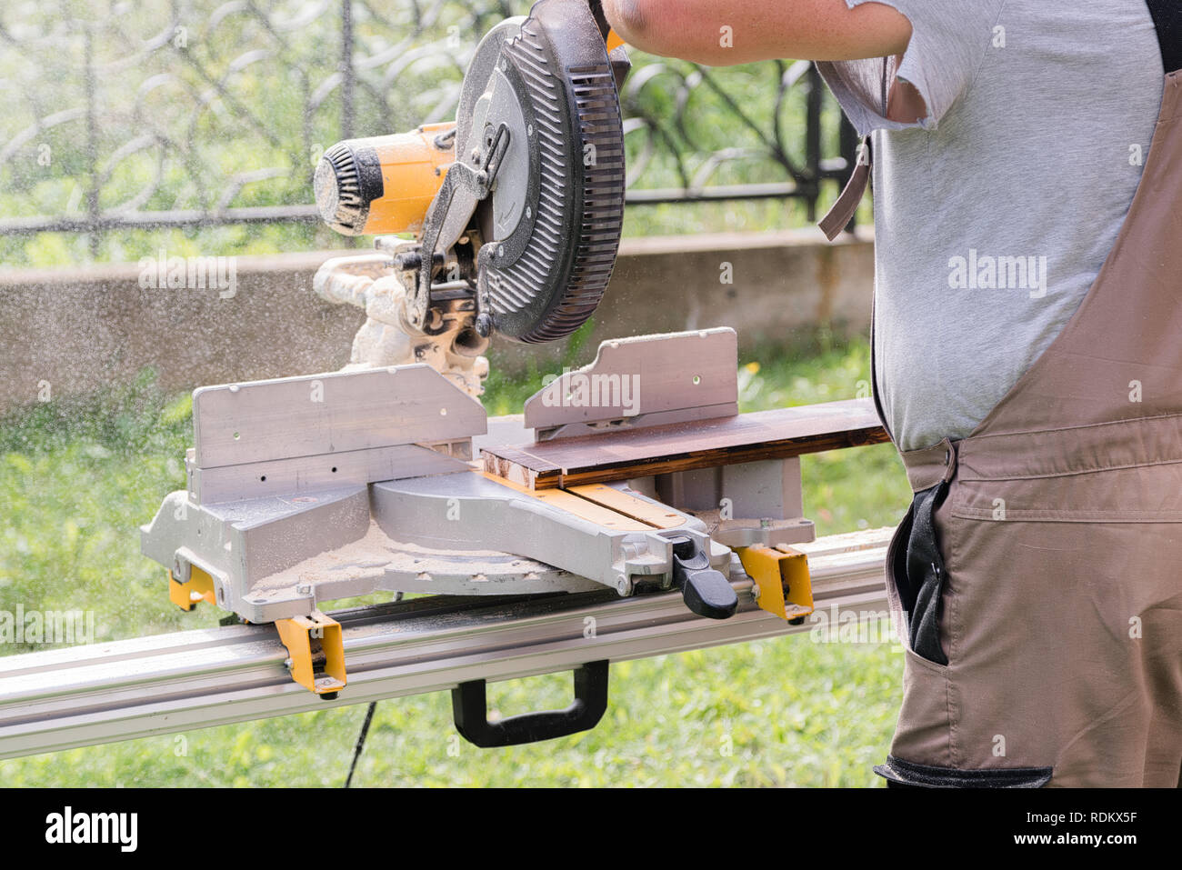 Master carpenter at work in the workshop outdoors. Carpenter hand sawing wood with table wood cutter saw - Stock Image