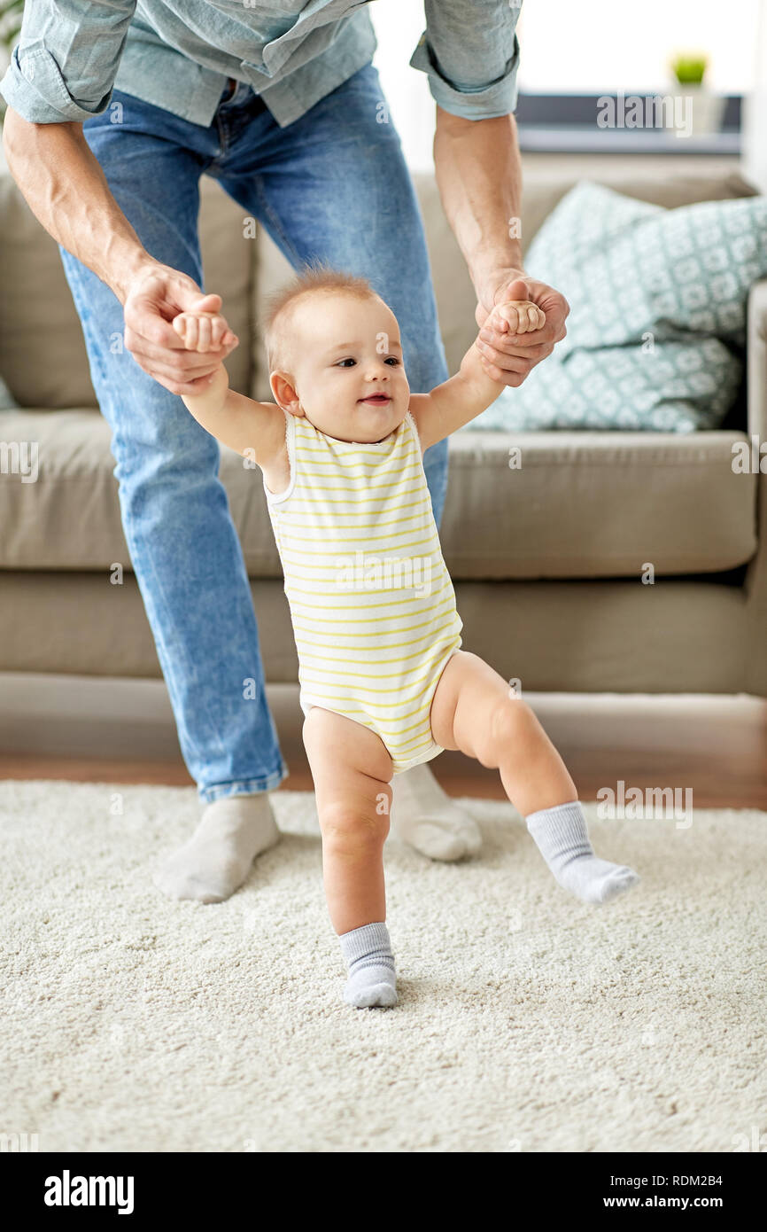 father helping baby daughter with walking at home - Stock Image