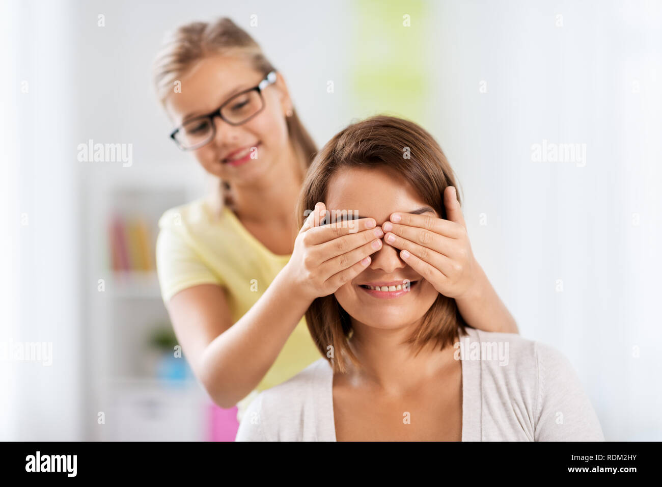 happy mother and daughter playing guess who game - Stock Image