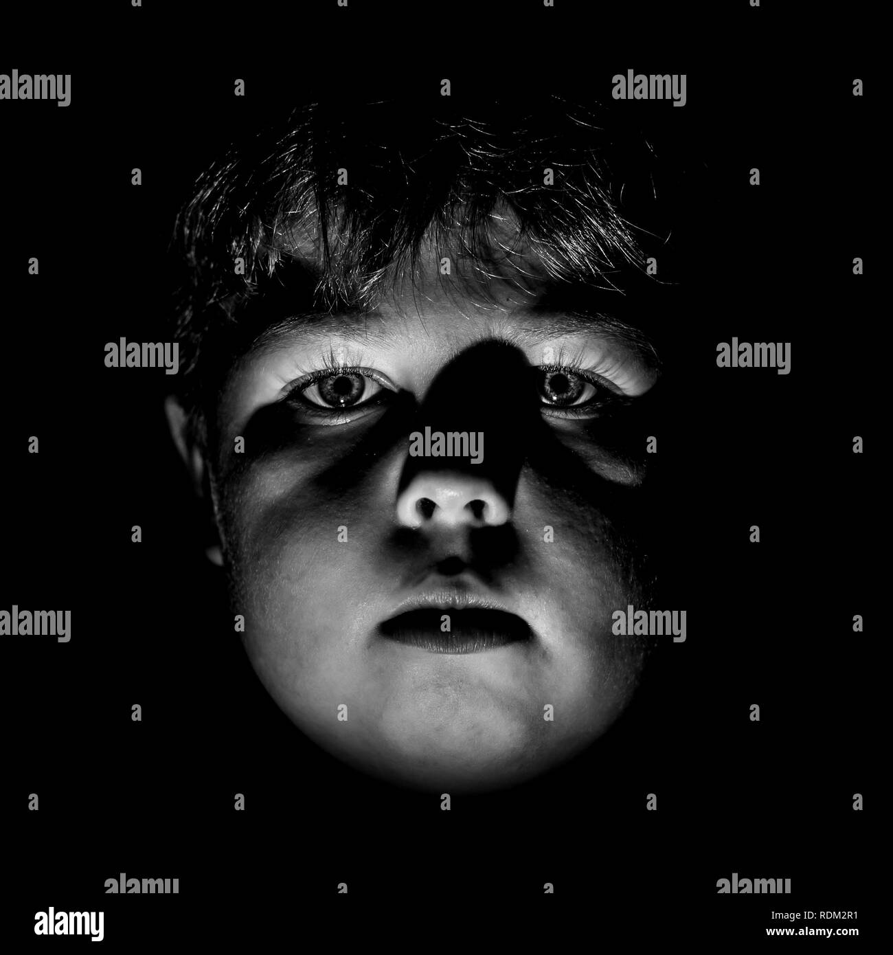 Portrait of calm young caucasian boy. Black and white shot, low key lighting. Isolated on black. - Stock Image