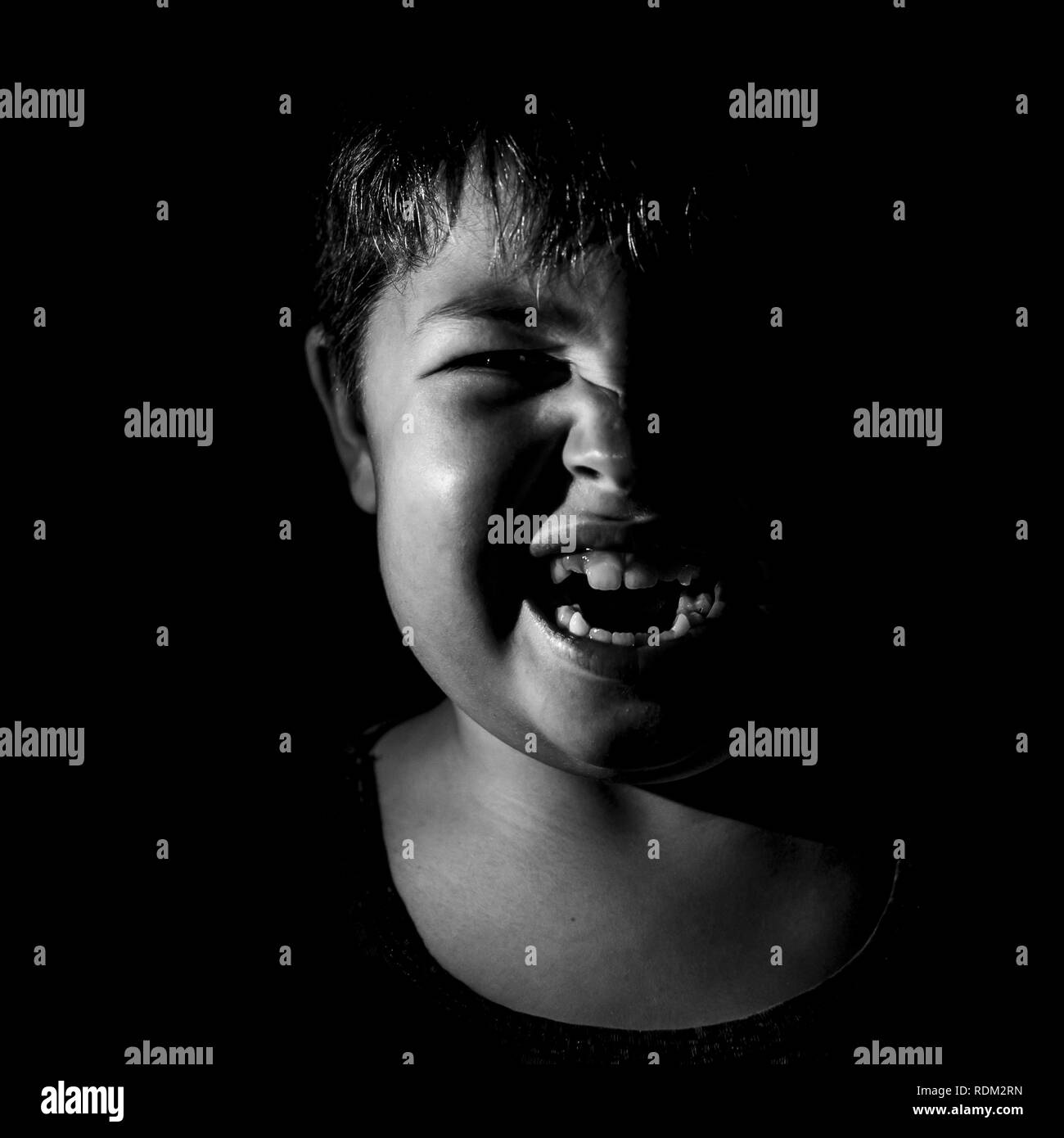 Portrait of anger young caucasian boy. Scary and agression concept. Black and white shot, low key lighting. Isolated on black. - Stock Image