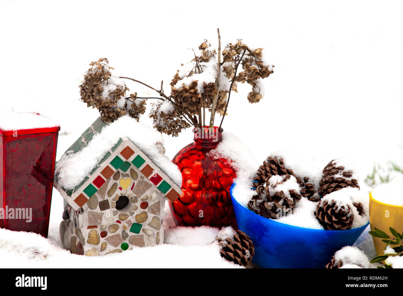 Snow-covered Birdhouse and Colorful vases and containers with Pinecones and Dried Flowers - Stock Image