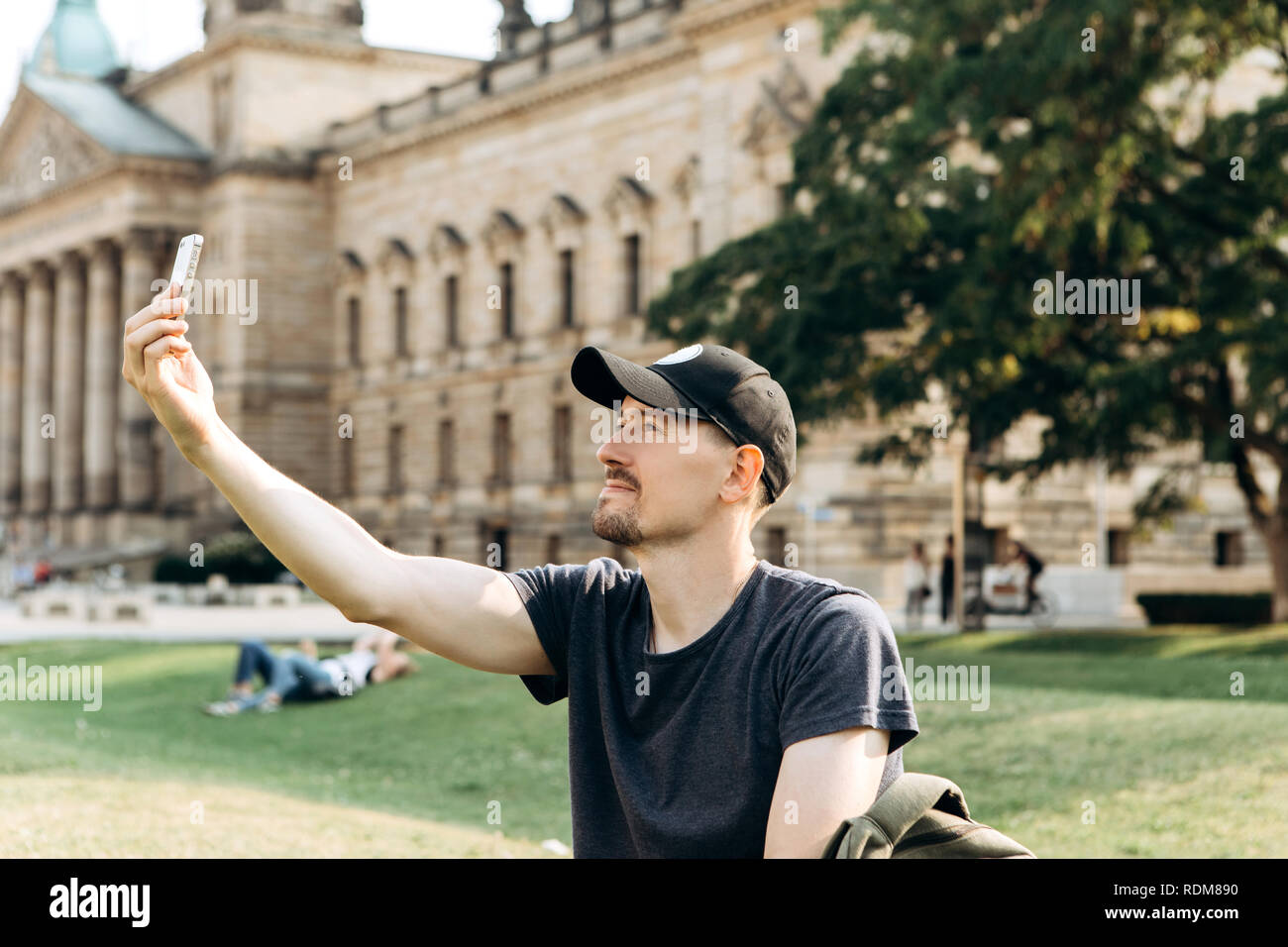 A young male tourist or student sits on the grass outside in Leipzig, Germany, talking on video or using a mobile phone to chat or take pictures. - Stock Image