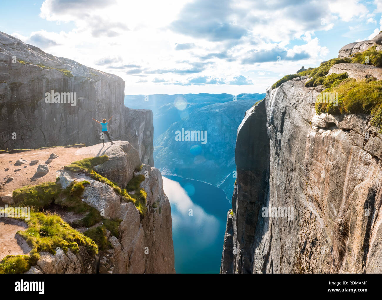 Woman on Kjeragbolten Travel in Norway Kjerag mountains, extreme vacations, adventure, tourist, happy emotions, success concept - Stock Image