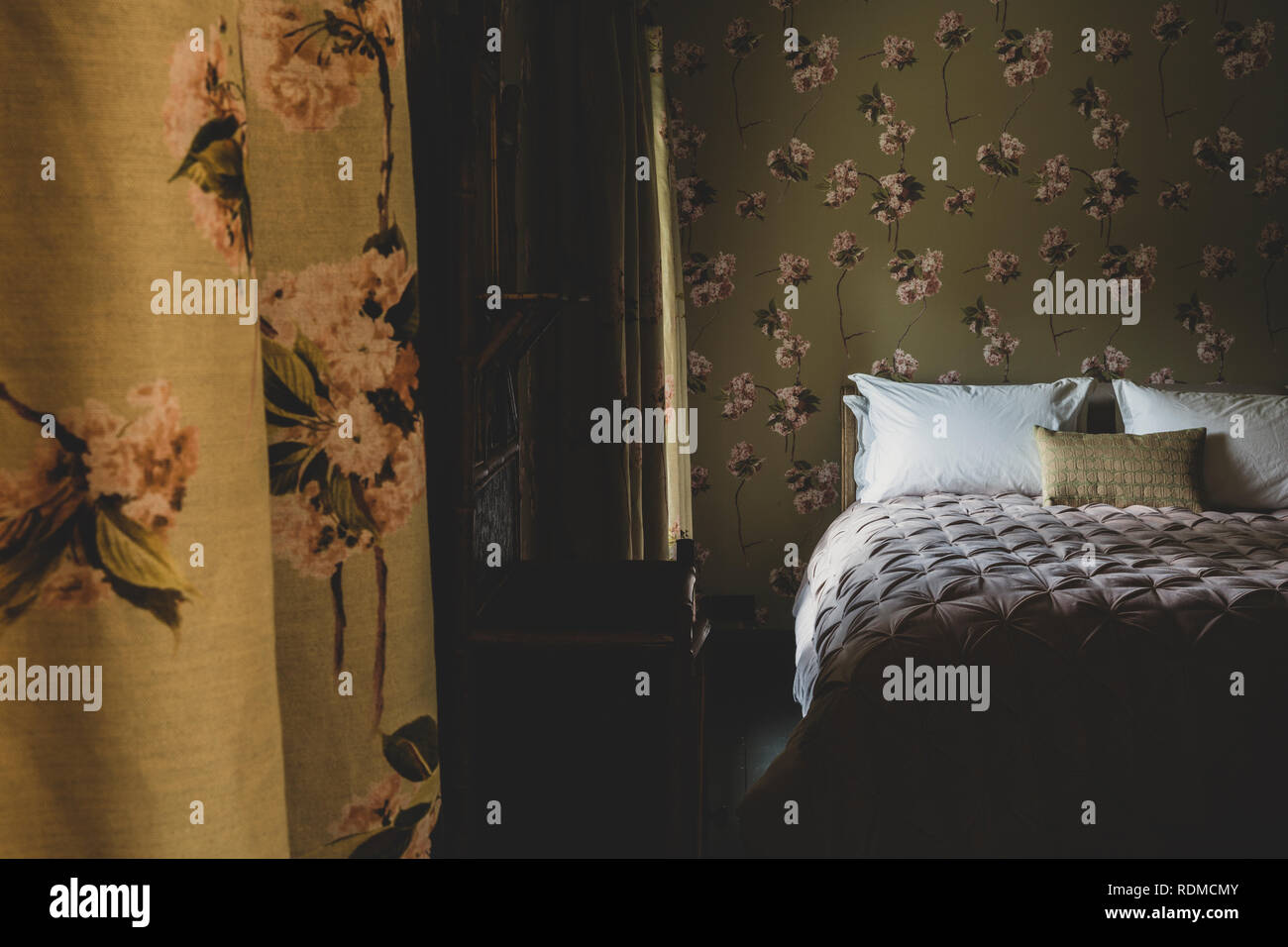 Interior view of bedroom with curtains and wallpaper with floral ...