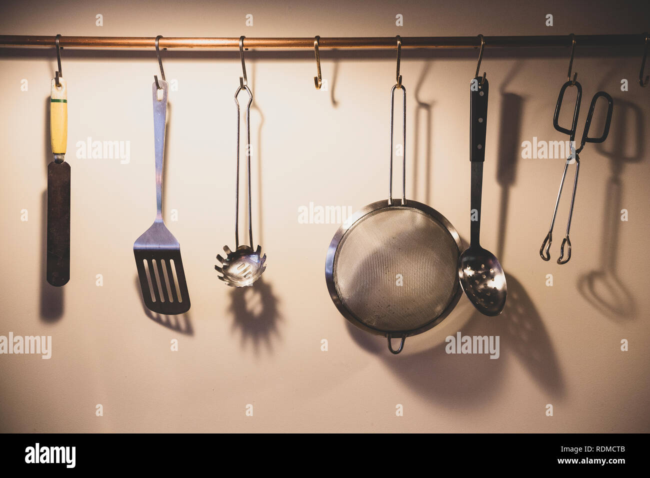 Close Up Of Kitchen Utensils Suspended From Copper Pipe Stock Photo Alamy
