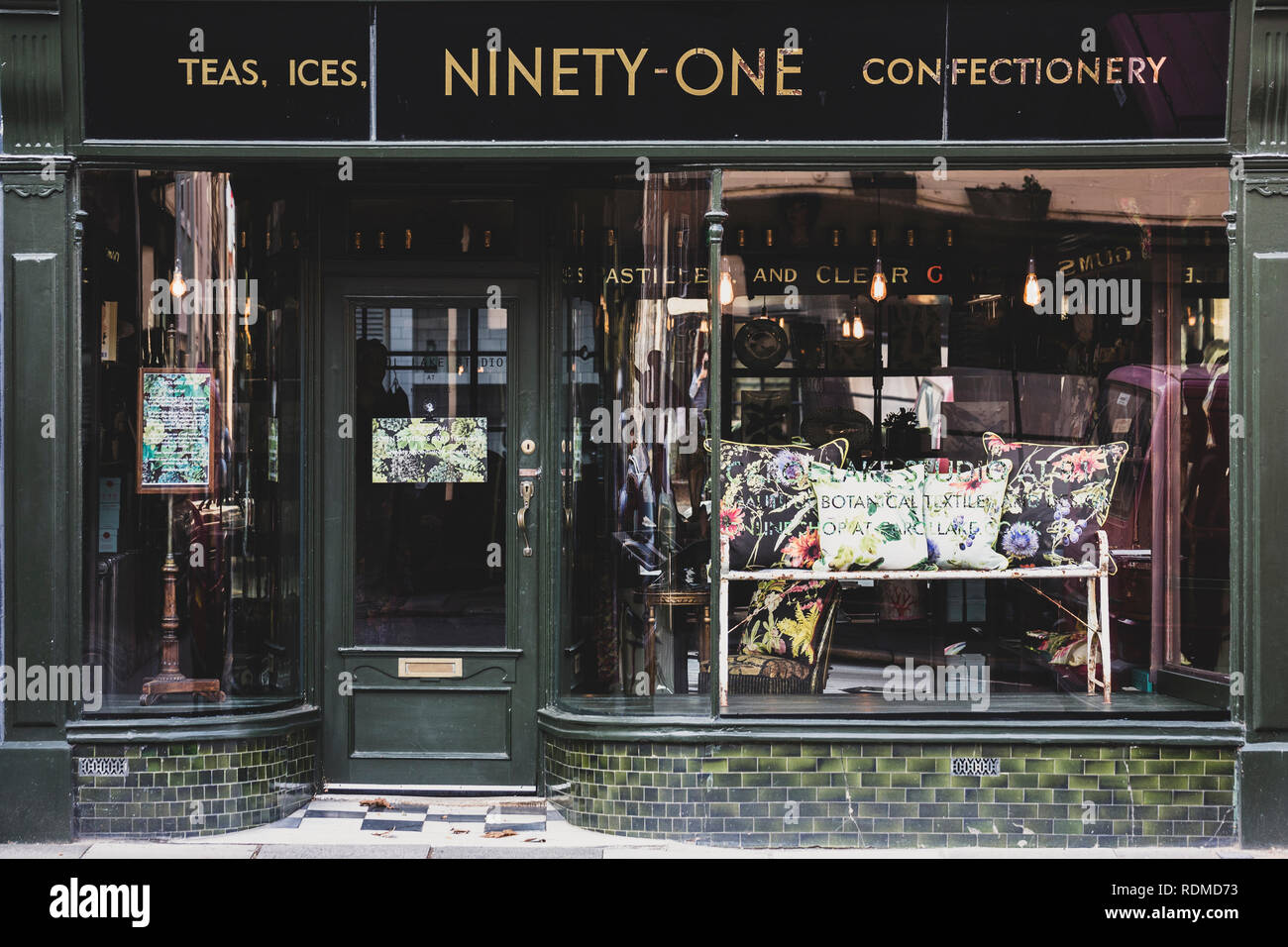 Exterior View Of Interior Design Store With Floral Print Cushions On  Vintage Metal Bench In Shop Window.