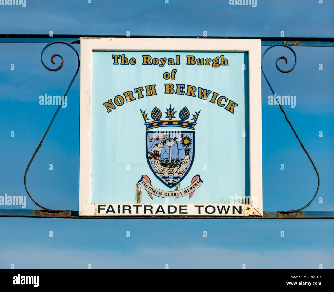 Roadside worn sign on road into North Berwick, with Royal Burgh of North Berwick, Faritrade Town, East Lothian, Scotland, UK - Stock Image