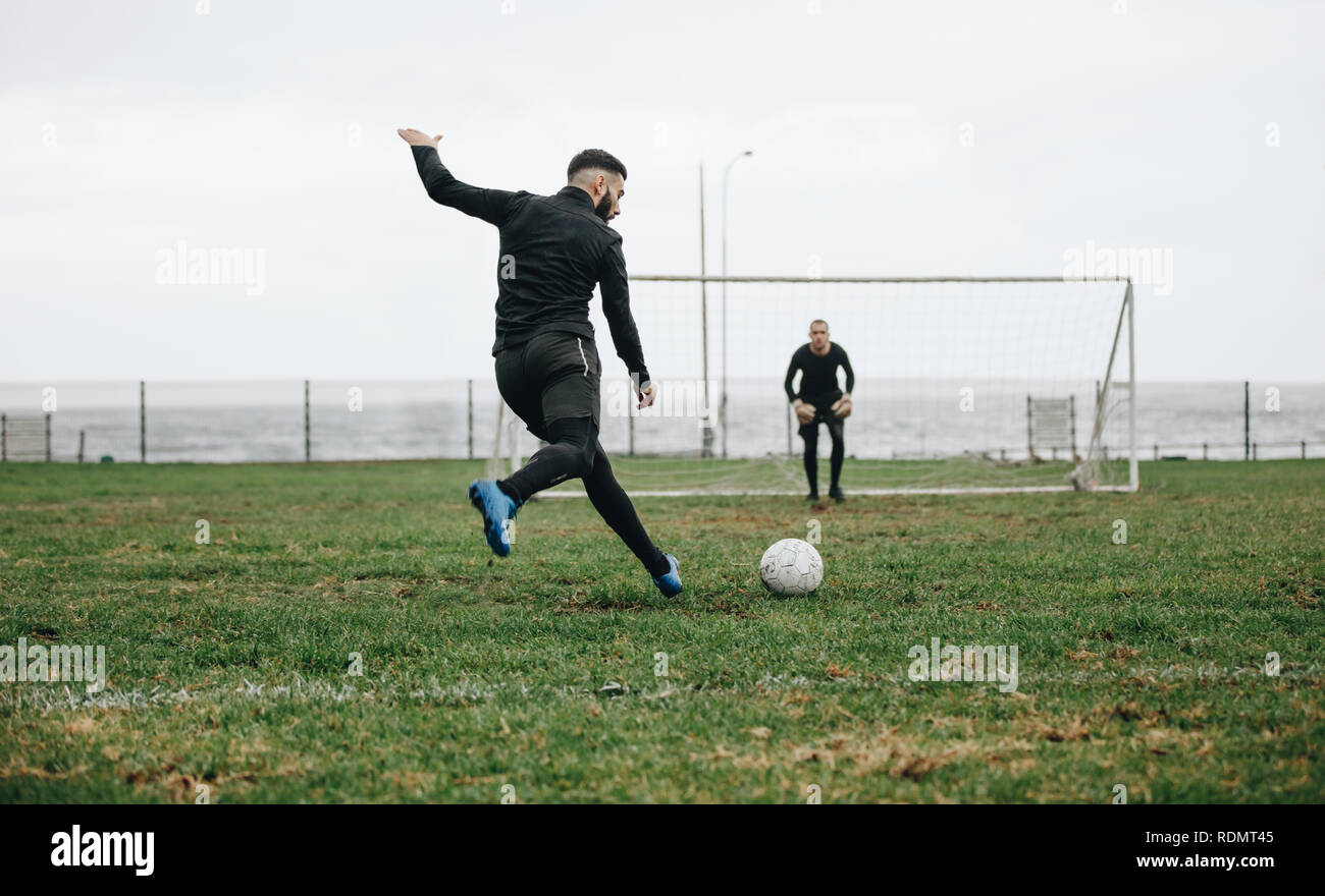 Footballer kicking a penalty shot. Soccer player kicking the ball towards the goal post with the goalkeeper in position. - Stock Image