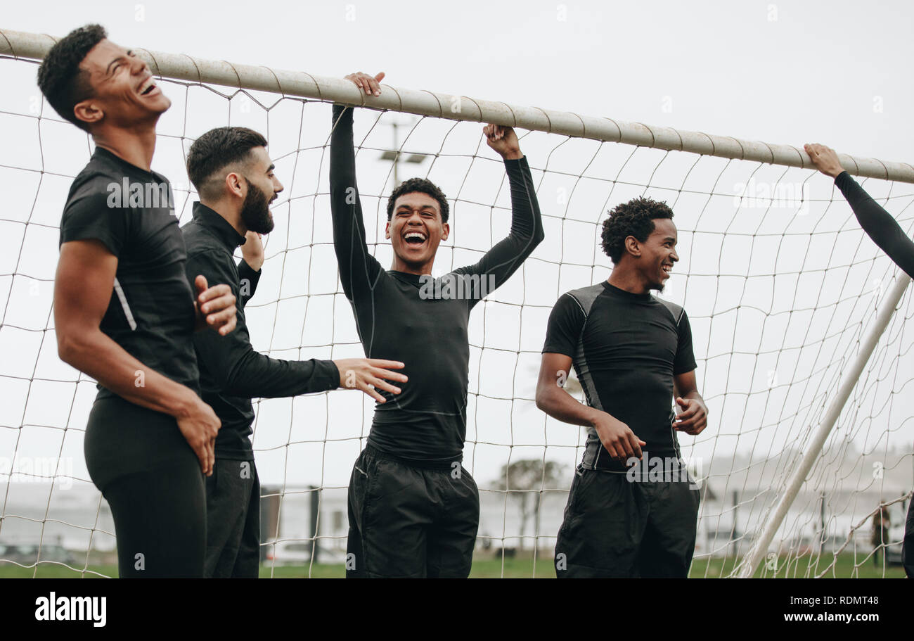 Soccer players standing near the goalpost relaxing and laughing. Footballers taking a break during a football match talking and laughing. - Stock Image