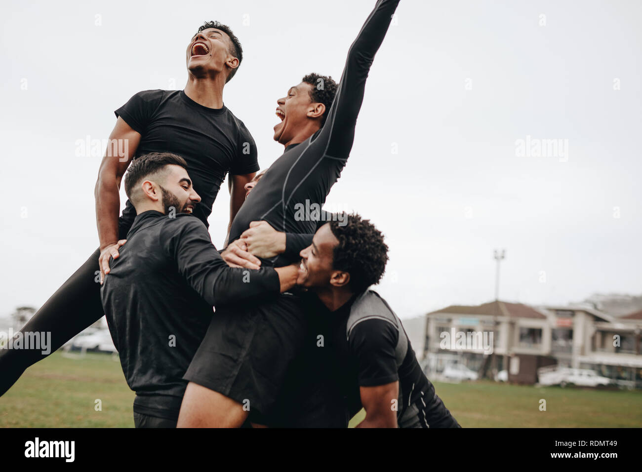 Excited soccer players shouting in joy after scoring a goal. Teammates celebrating victory holding the goal scorer. - Stock Image