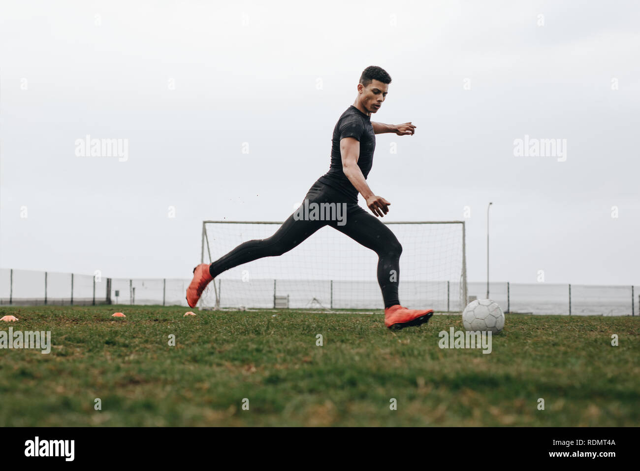 Soccer player in position to kick a football. Footballer practicing his game on field early in the morning. - Stock Image