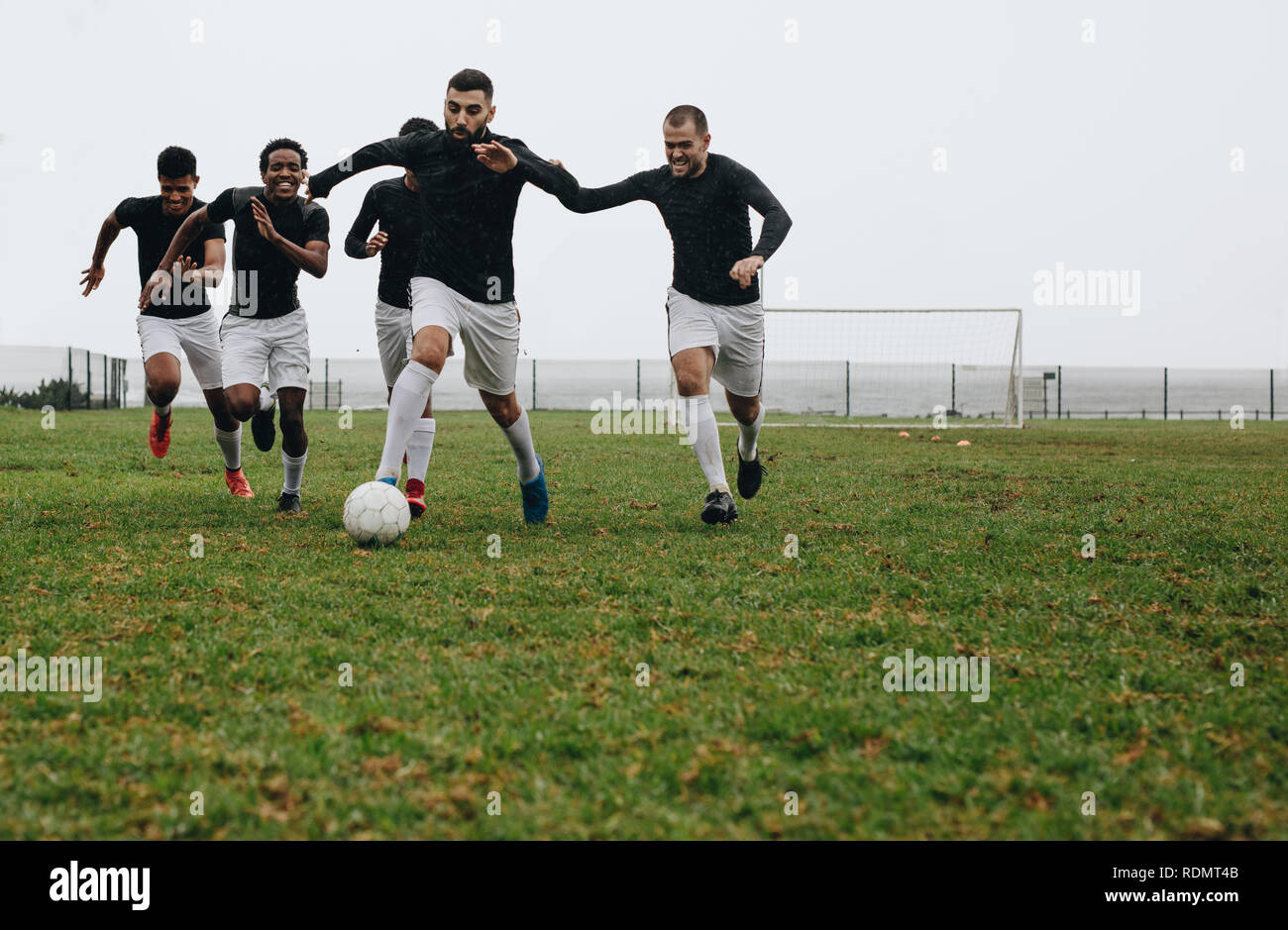Football players practicing on field in the morning. Footballer kicking and running with the ball while other players run behind to take possession. - Stock Image
