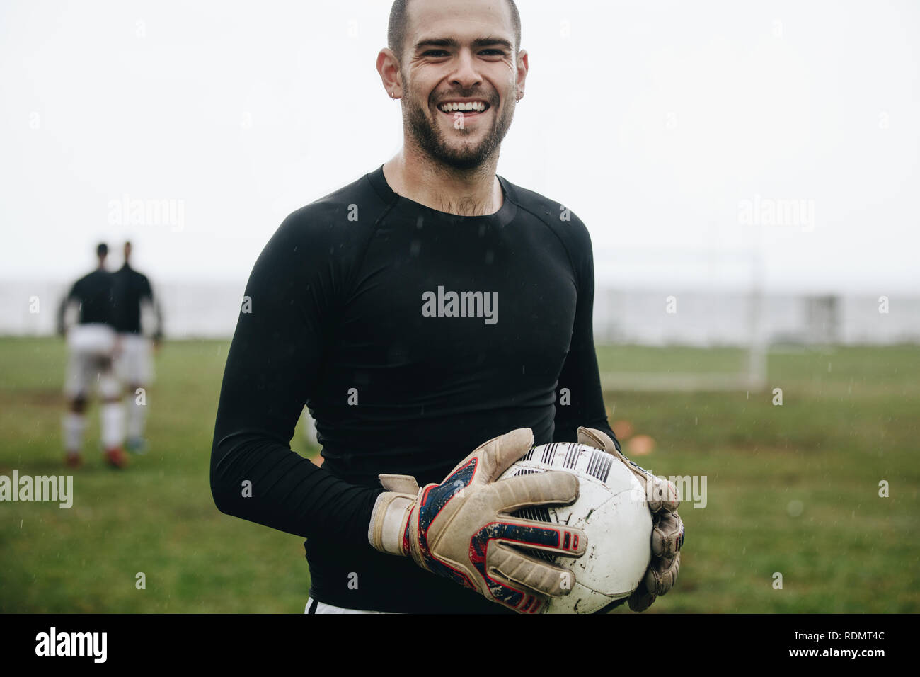 Portrait of a cheerful goalkeeper standing with a soccer ball in hand. Soccer player standing on field holding a football practicing in the morning. - Stock Image