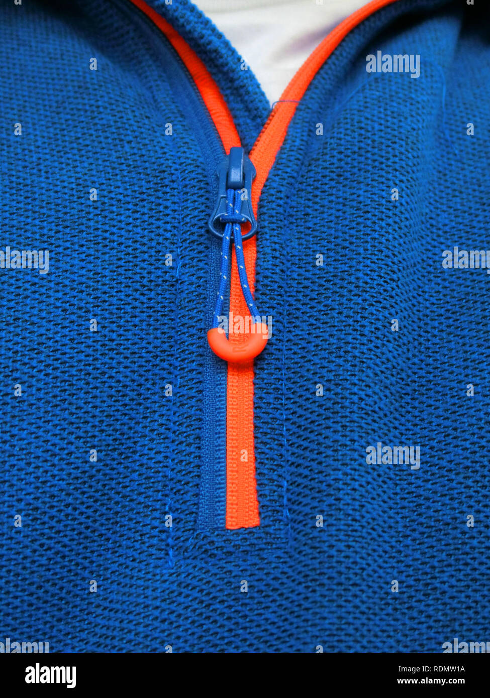 Orange Zip Fastner With Toggle or Zipper on a Man's Blue Sweatshirt Clothing - Stock Image