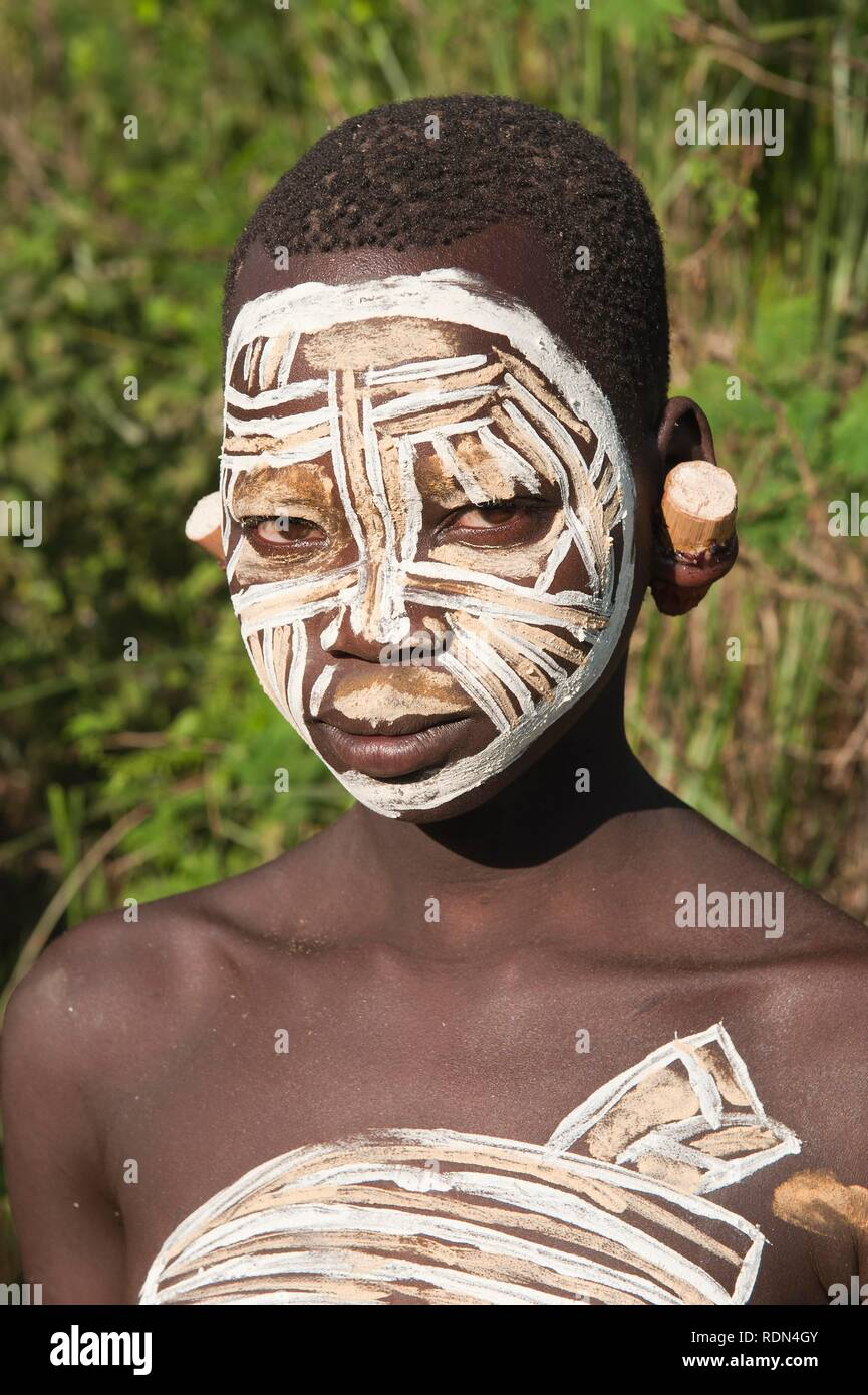 Surma Woman with facial and body painting and earlobe plates, Kibish, Omo River Valley, Ethiopia, Africa - Stock Image