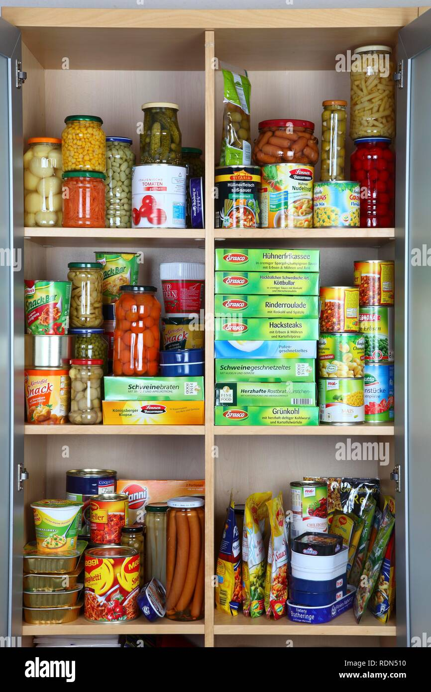 Cupboard filled with various packaged foods in glass jars and tin cans - Stock Image