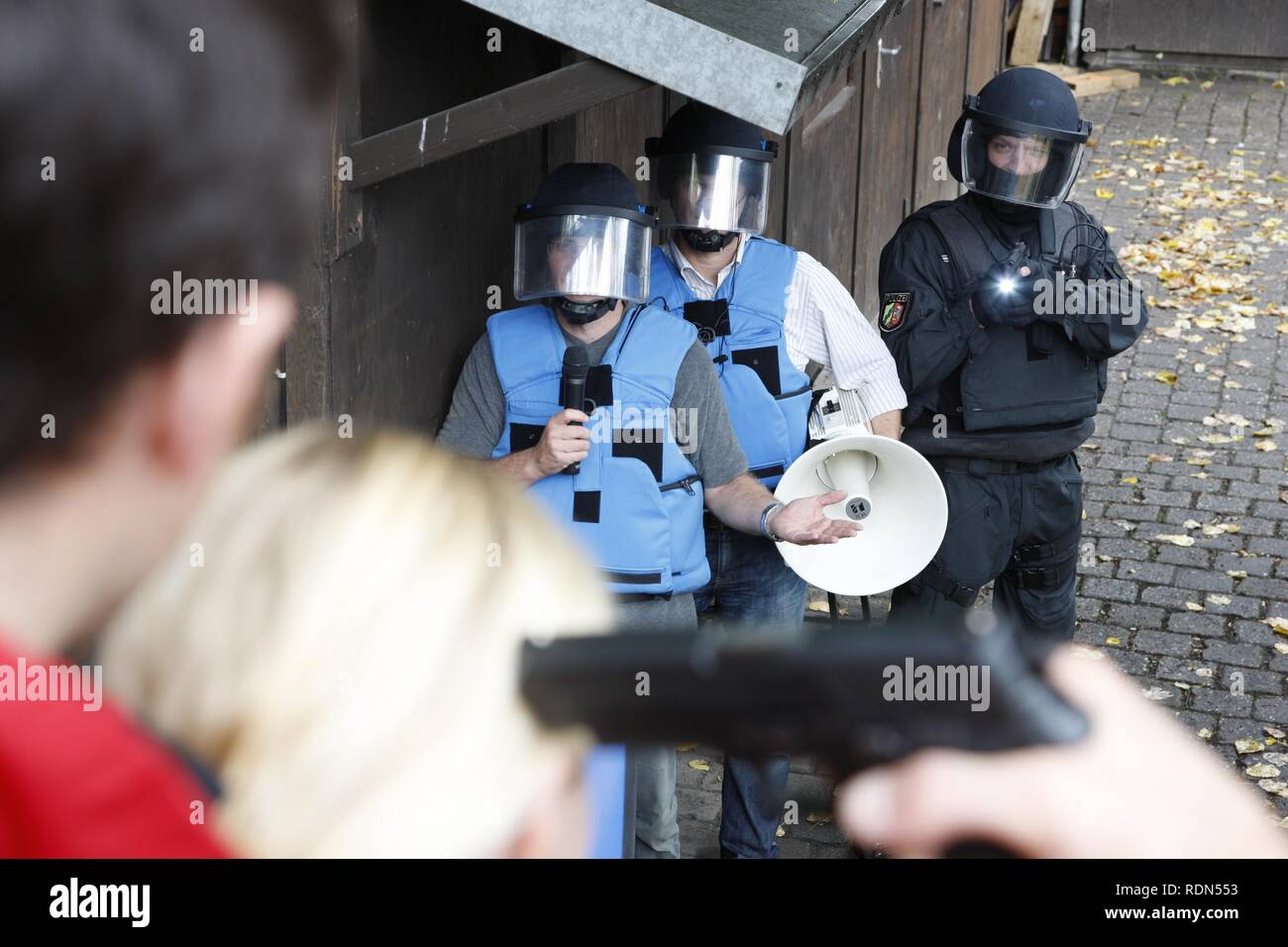 Special police unit negotiation group, operational rehearsal, a criminal is threatening a hostage with a gun, negotiators are - Stock Image