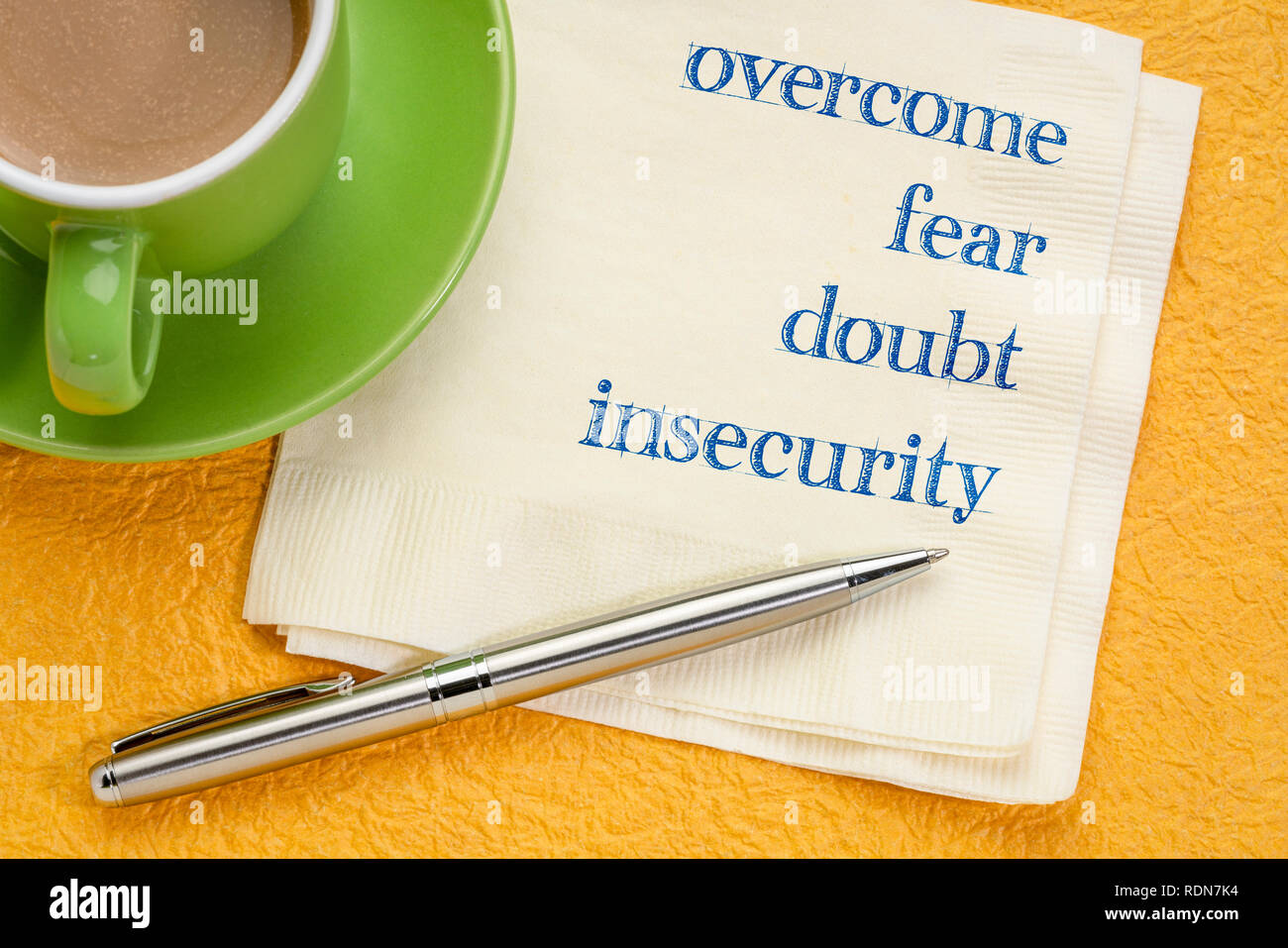 overcome fear, doubt, insecurity - handwriting on a napkin with a cup of coffee - Stock Image