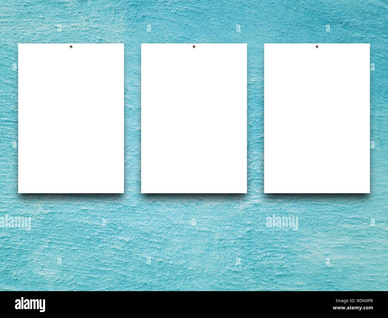 Three blank frames on aqua concrete wall background - Stock Image
