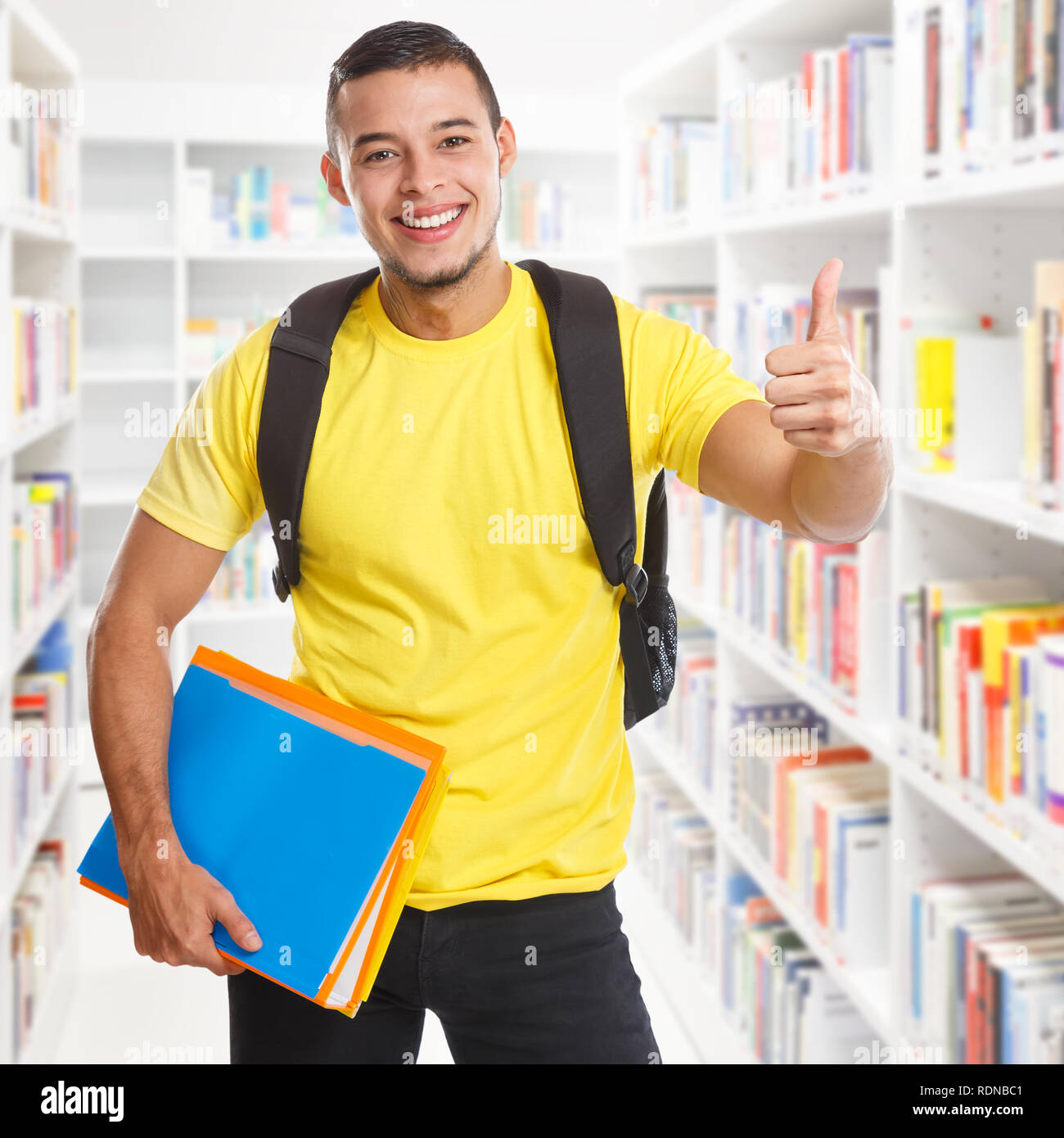 Student young man success successful library square learning thumbs up smiling people learn - Stock Image