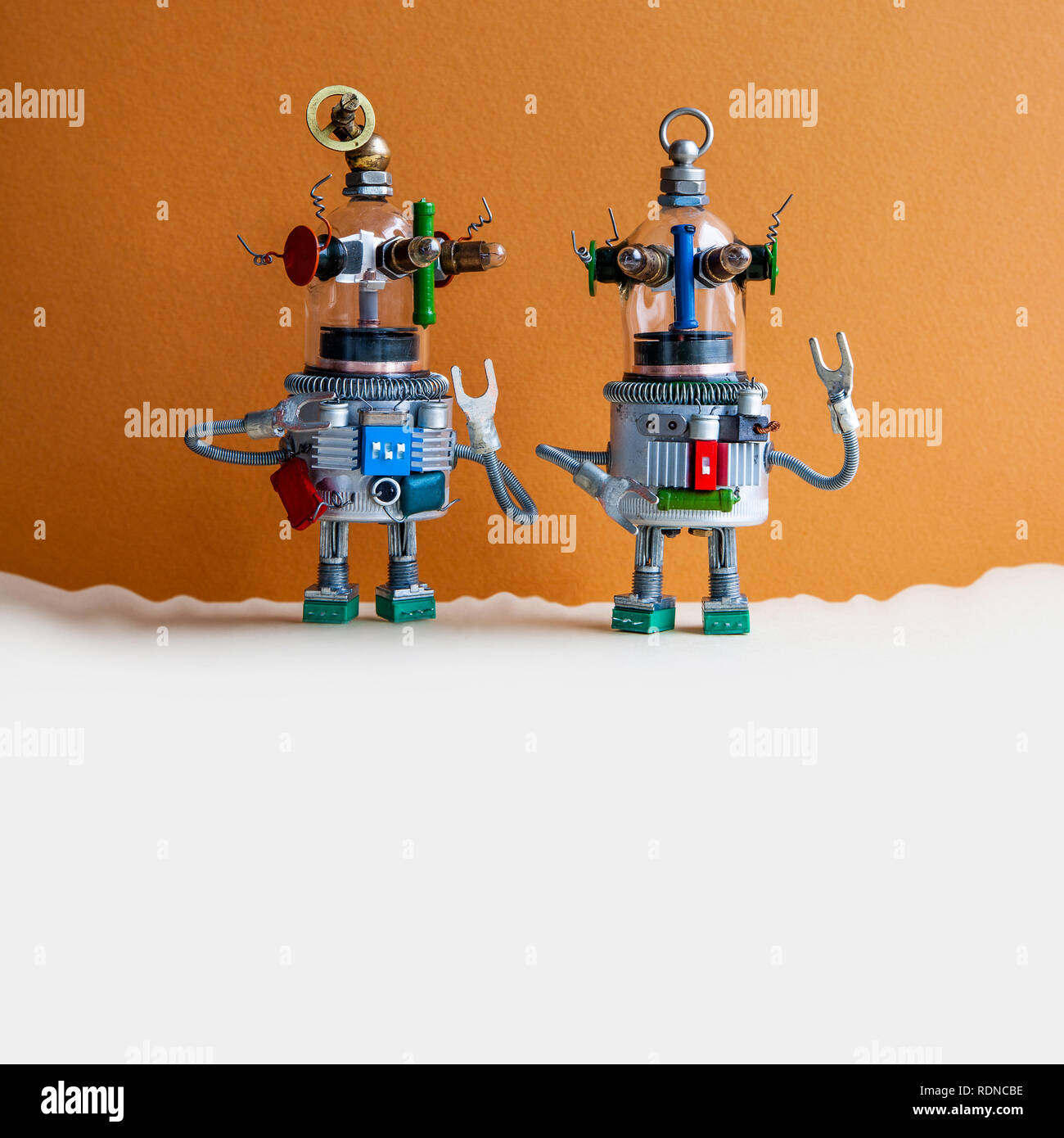 Two glass head ufo robots on brown beige background. Futuristic robot humanoid toys with raised hands. Copy space - Stock Image
