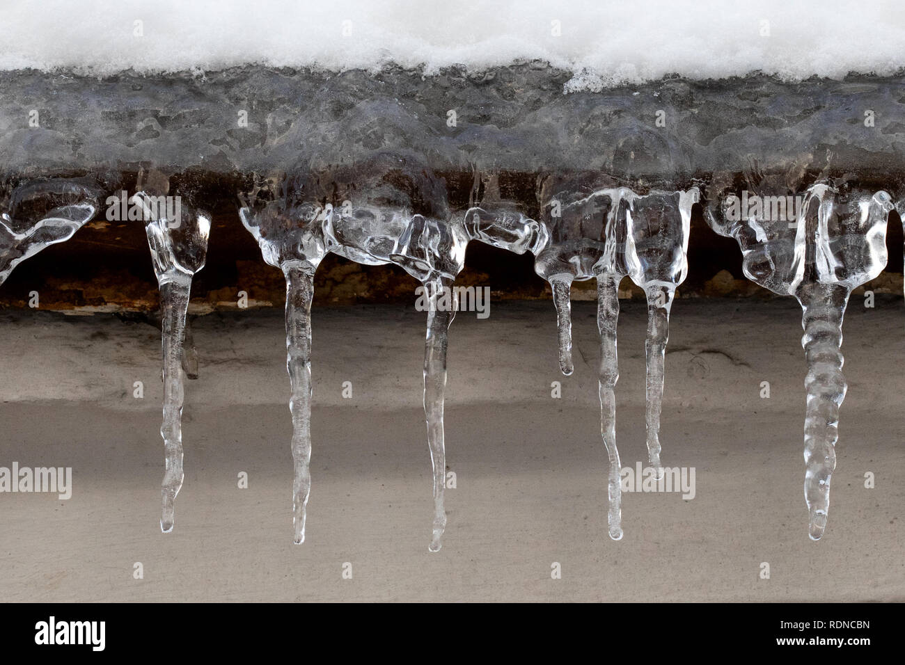 Small icicles spike of ice hanging from the roof element. Subfreezing weather concept. - Stock Image