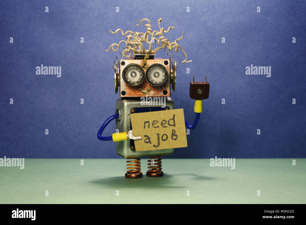 Robot looking for a job. The crazy unemployed toy robot holds cardboard announcement handwritten text Need a job. Blue green background. - Stock Image