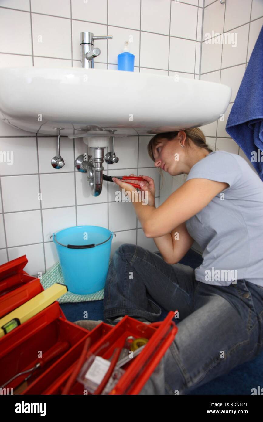 Young woman repairing a defective water faucet in a bathroom - Stock Image