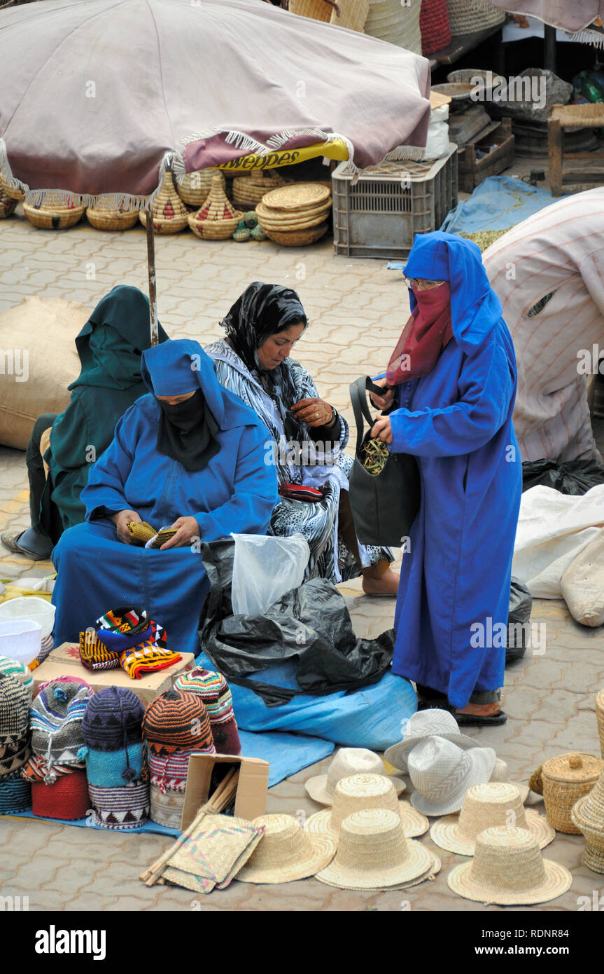 Veiled Muslim Women or Moroccan Woman in Burka Shopping in Market or Souk Marrakesh or Marrakech Morocco - Stock Image