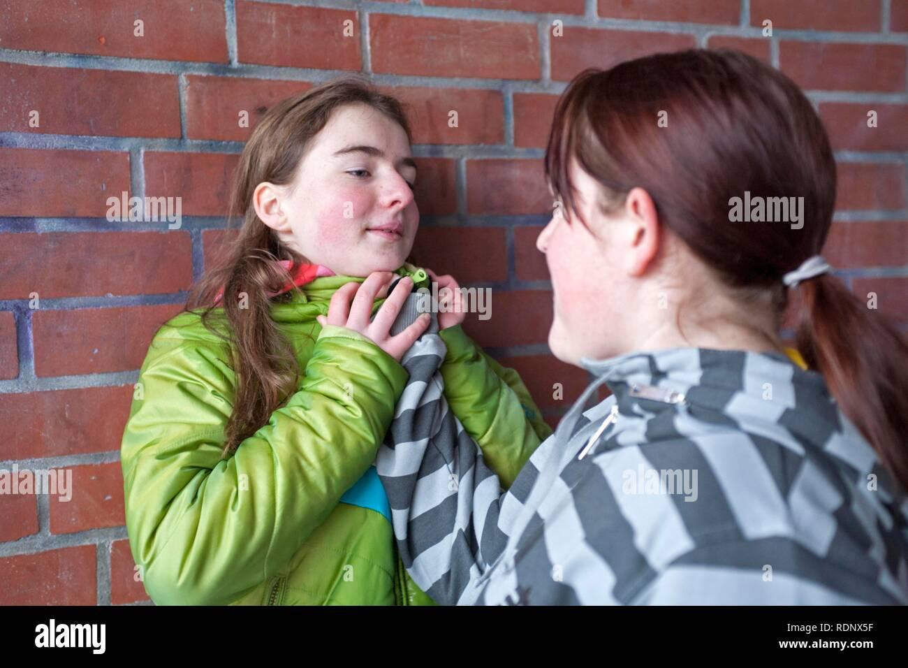 Girl pushing a smaller girl brutally against a wall, posed scene - Stock Image