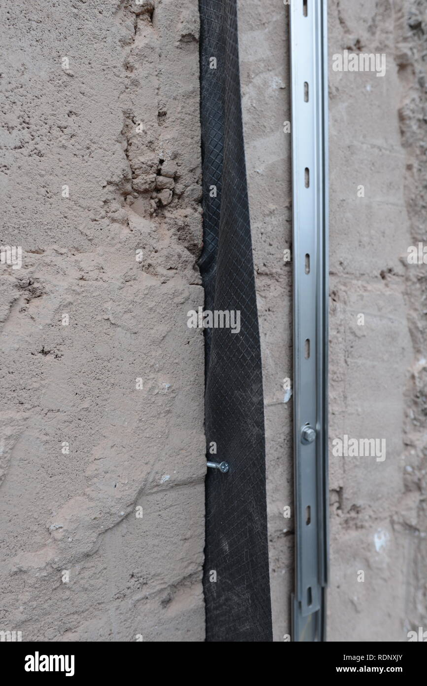 Construction detail of new vertical damp proof course for home extension. - Stock Image