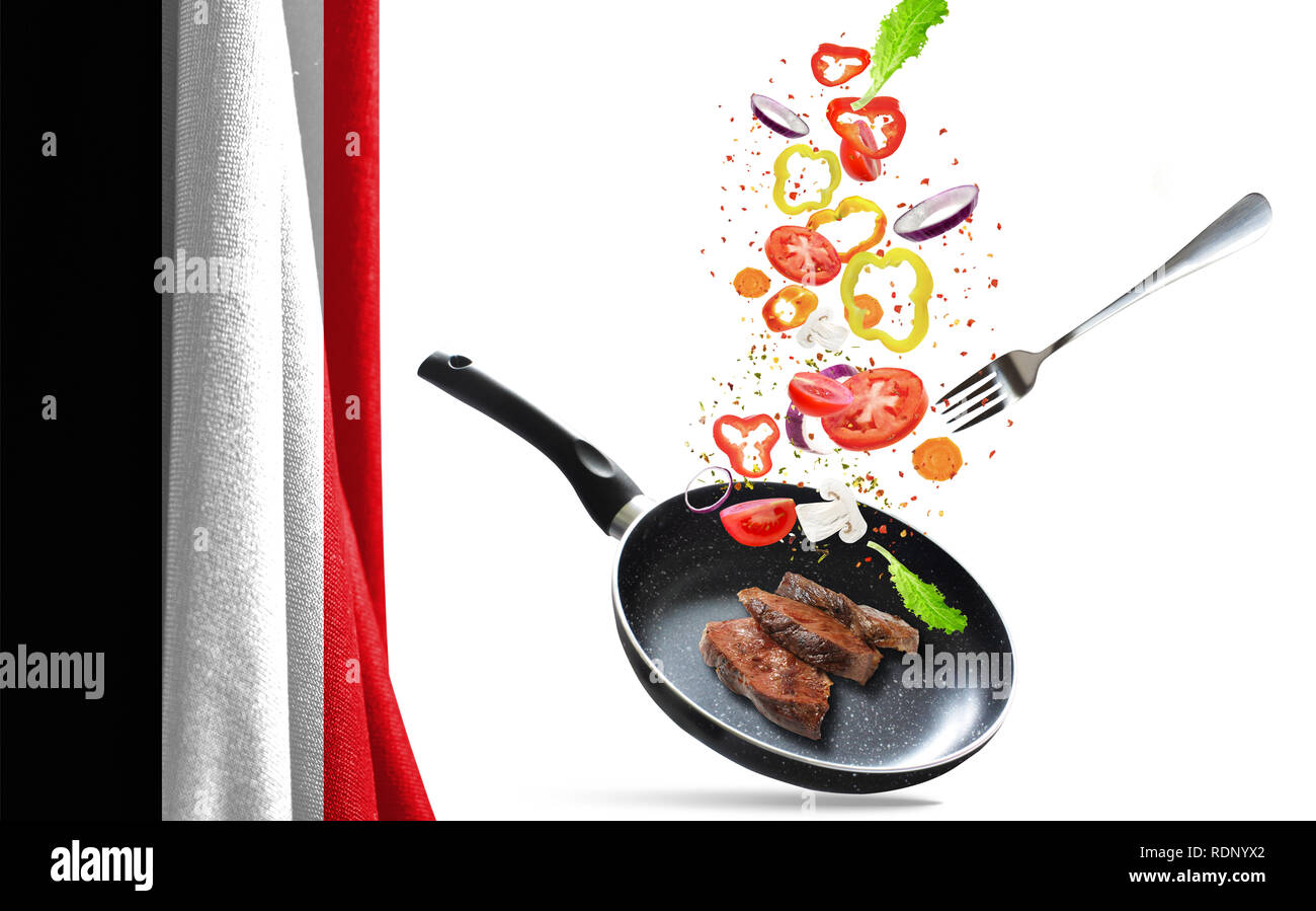 Frying pan with falling vegetables and meat, isolated objects. On the background of the flag of Yemen - Stock Image