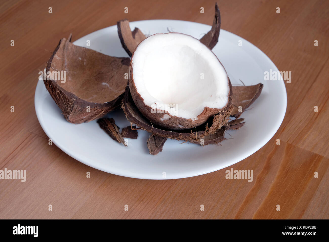 Still life with broken coconut shell ripe white flesh inside and debris on round white plate on brown wooden table horizontal close up photo - Stock Image