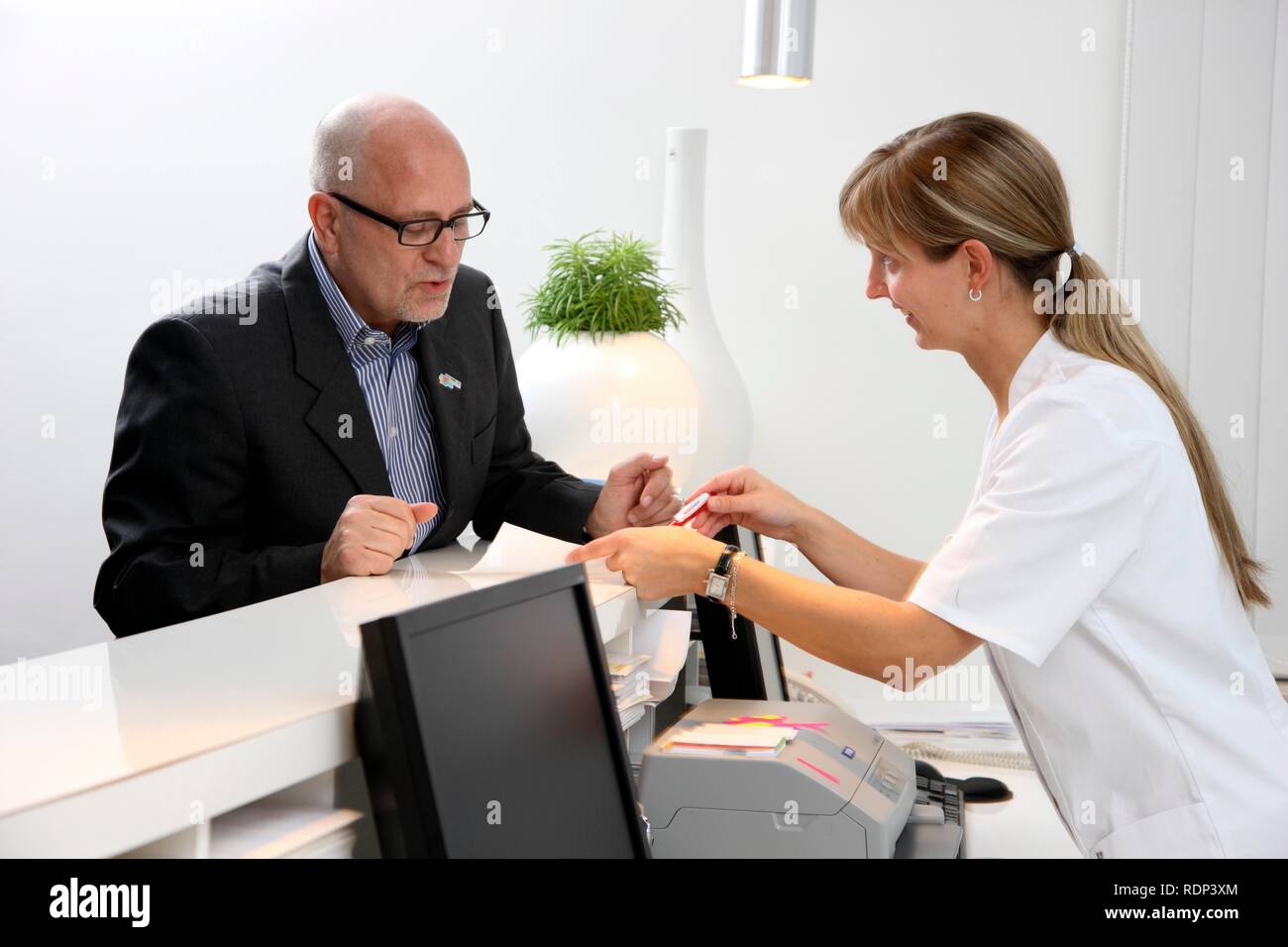 Medical practice, patient at the reception, talking to a nurse - Stock Image