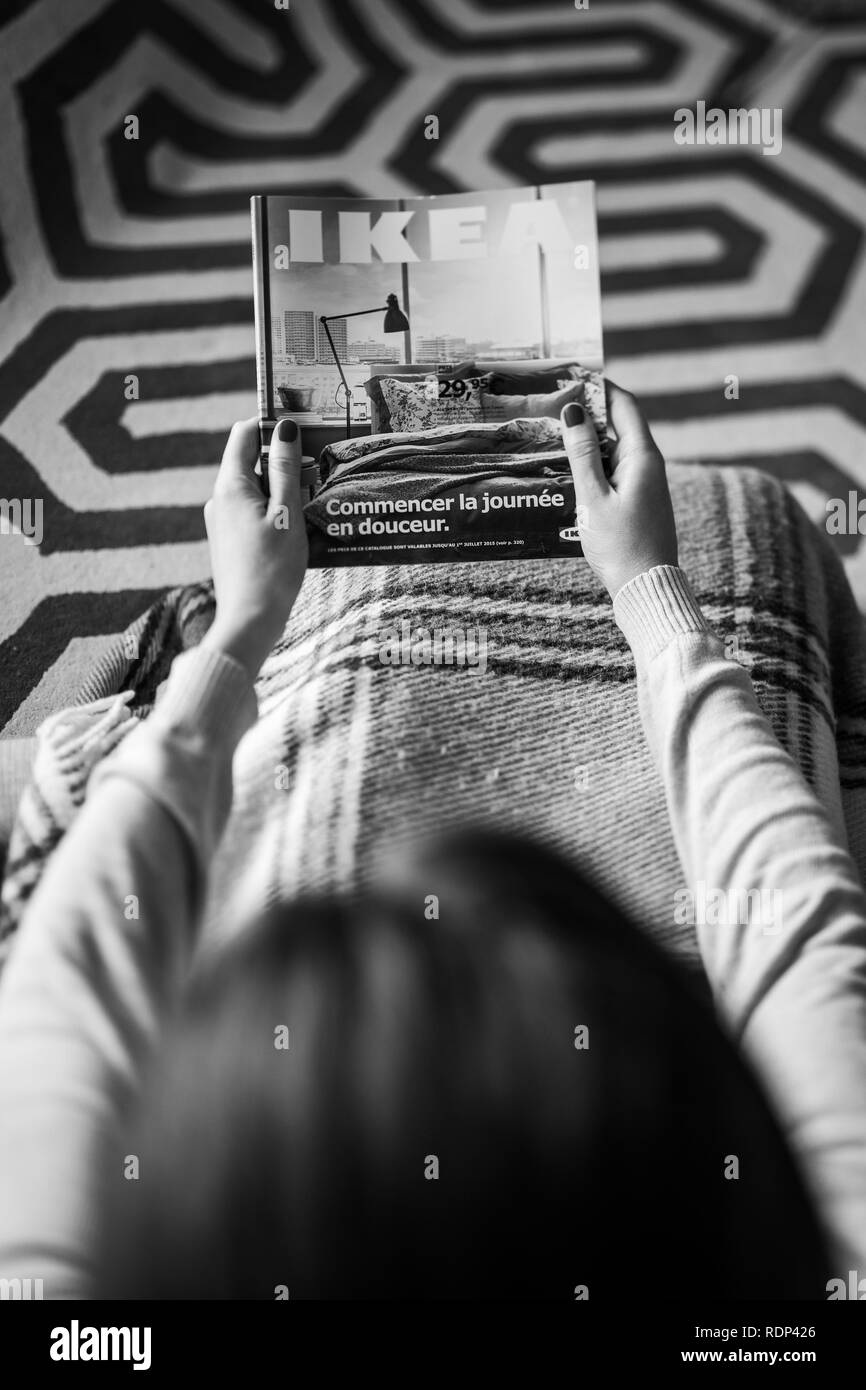 PARIS, FRANCE - AUGUST 24, 2014: View from above of woman reading IKEA Catalogue before buying new commode furniture for her new house - black and white - Stock Image