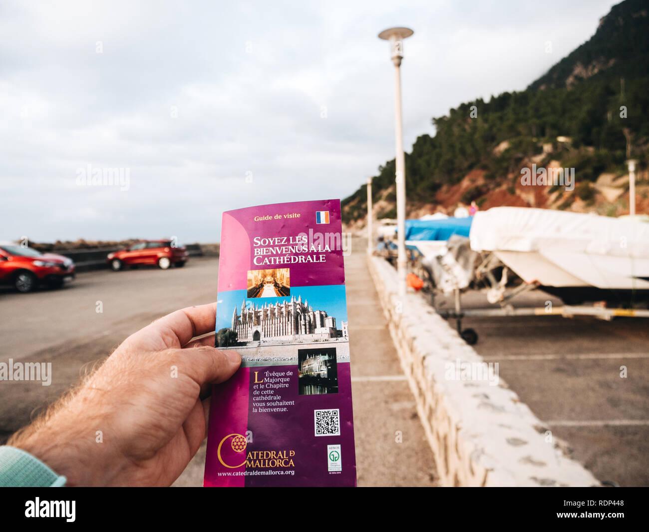 Port de Valldemosa, Palma de Malloca, Spain - May 10, 2018: Man holding pov the touristic guide of the Santa Maria of Palma Cathedral in the parking of Port de Valldemosa Stock Photo