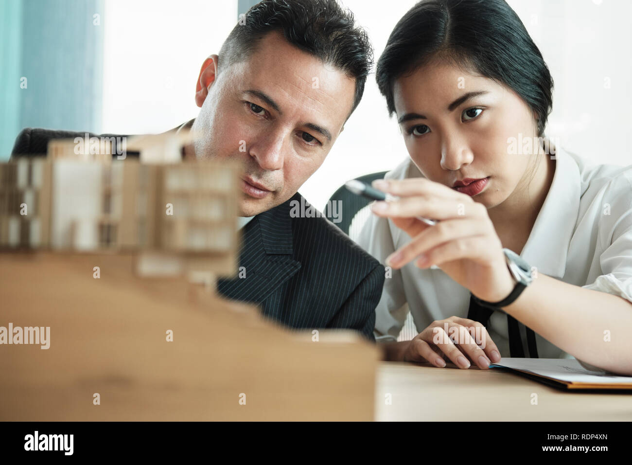 Confident Businessman Looking At Architecture Miniature House Project - Stock Image