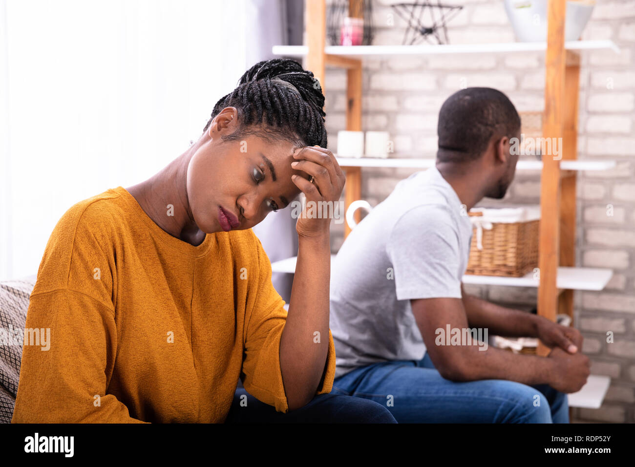Upset Young African Couple Sitting On Sofa Ignoring Each Other Stock Photo