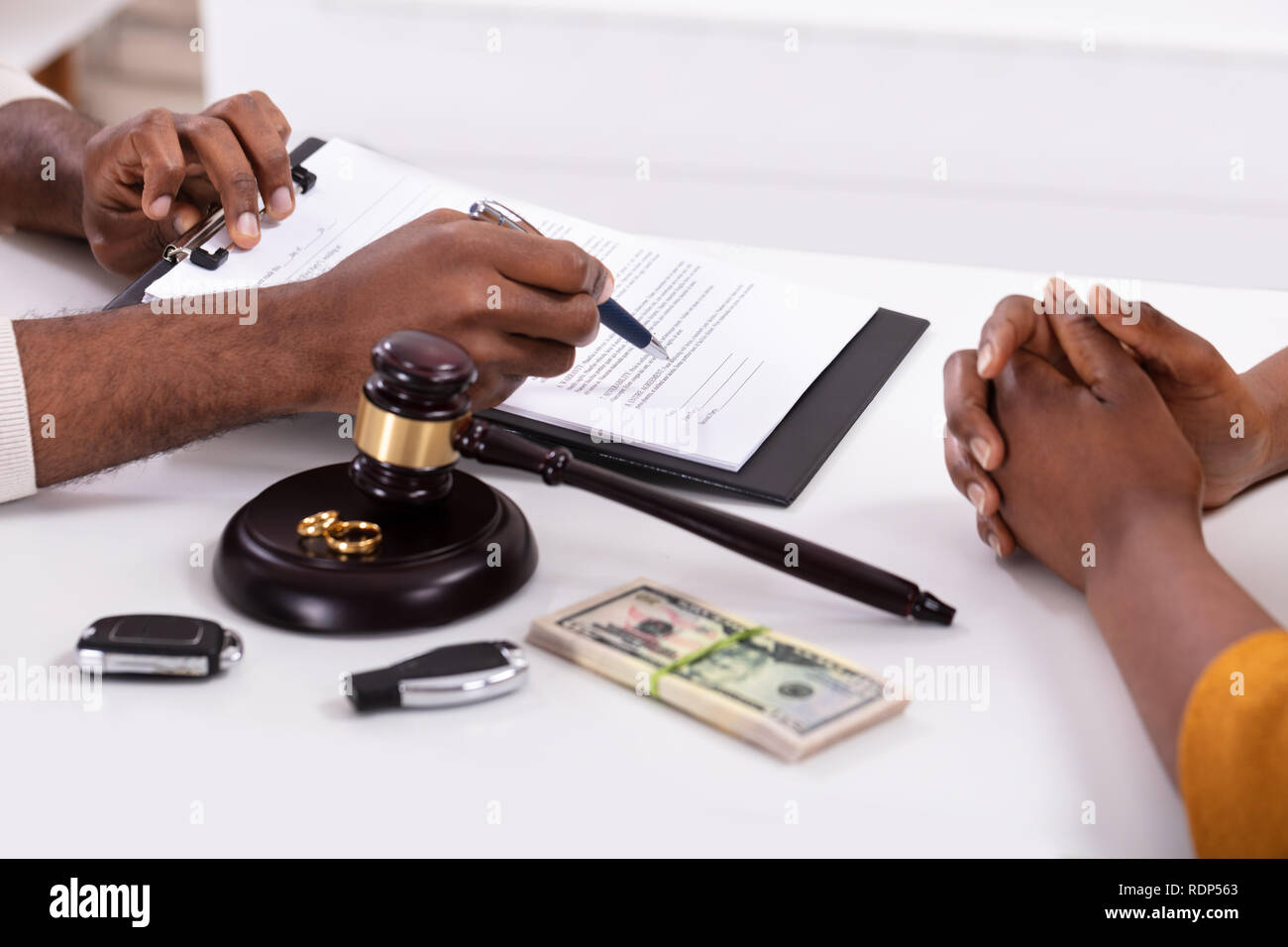 Judge Explaining Document To His Client With Golden Rings And Banknotes On Desk - Stock Image