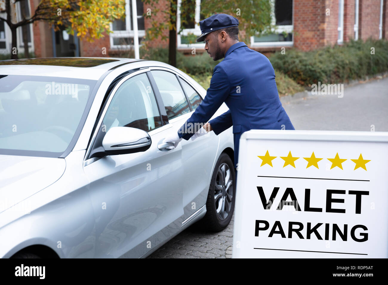 Happy Male Valet Opening Car Door Near Valet Parking Sign - Stock Image