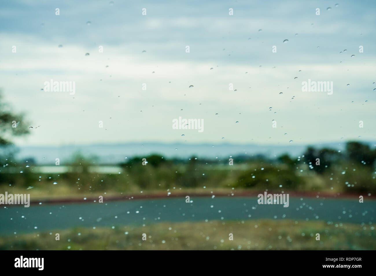 Drops of rain on the window; blurred landscape in the background - Stock Image