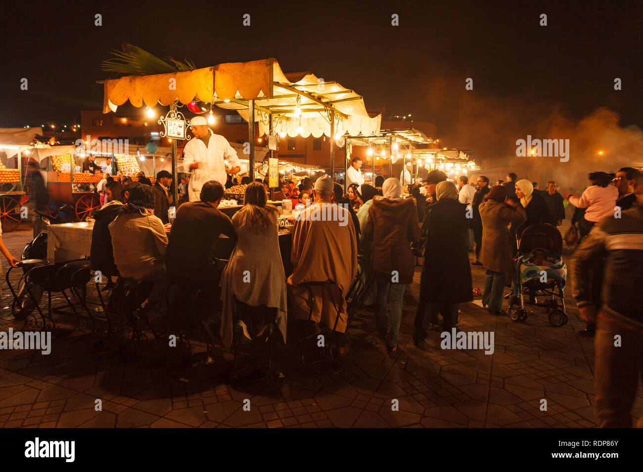 Families and tourists eating at food market stalls in Marrakesh - Stock Image