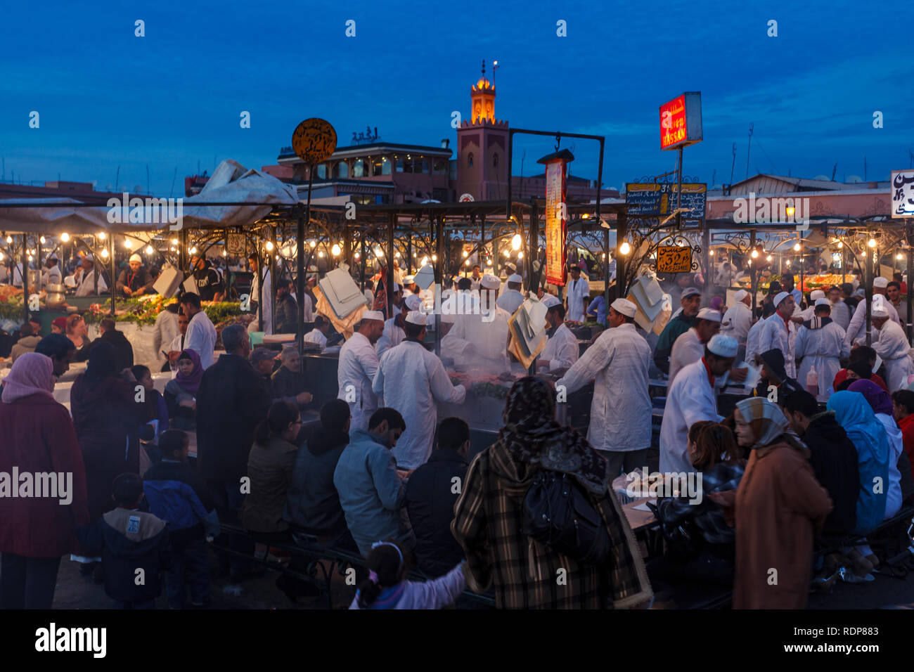Busy chefs an servers provide dinner for families and tourists  at food market stalls in Marrakesh - Stock Image