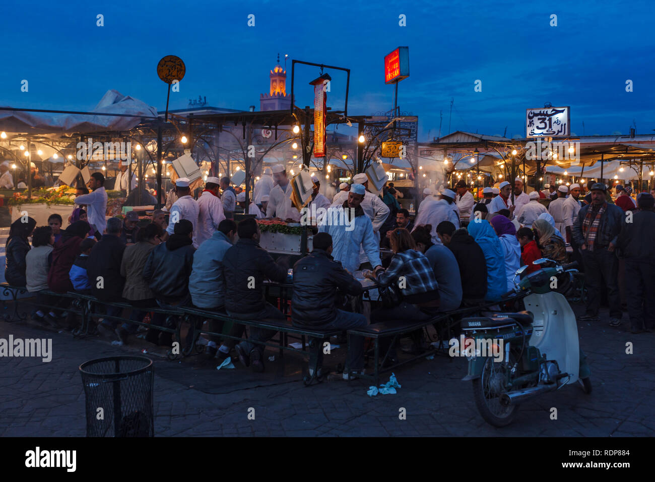 Families and tourists eating at crowded food market stalls in Marrakesh - Stock Image