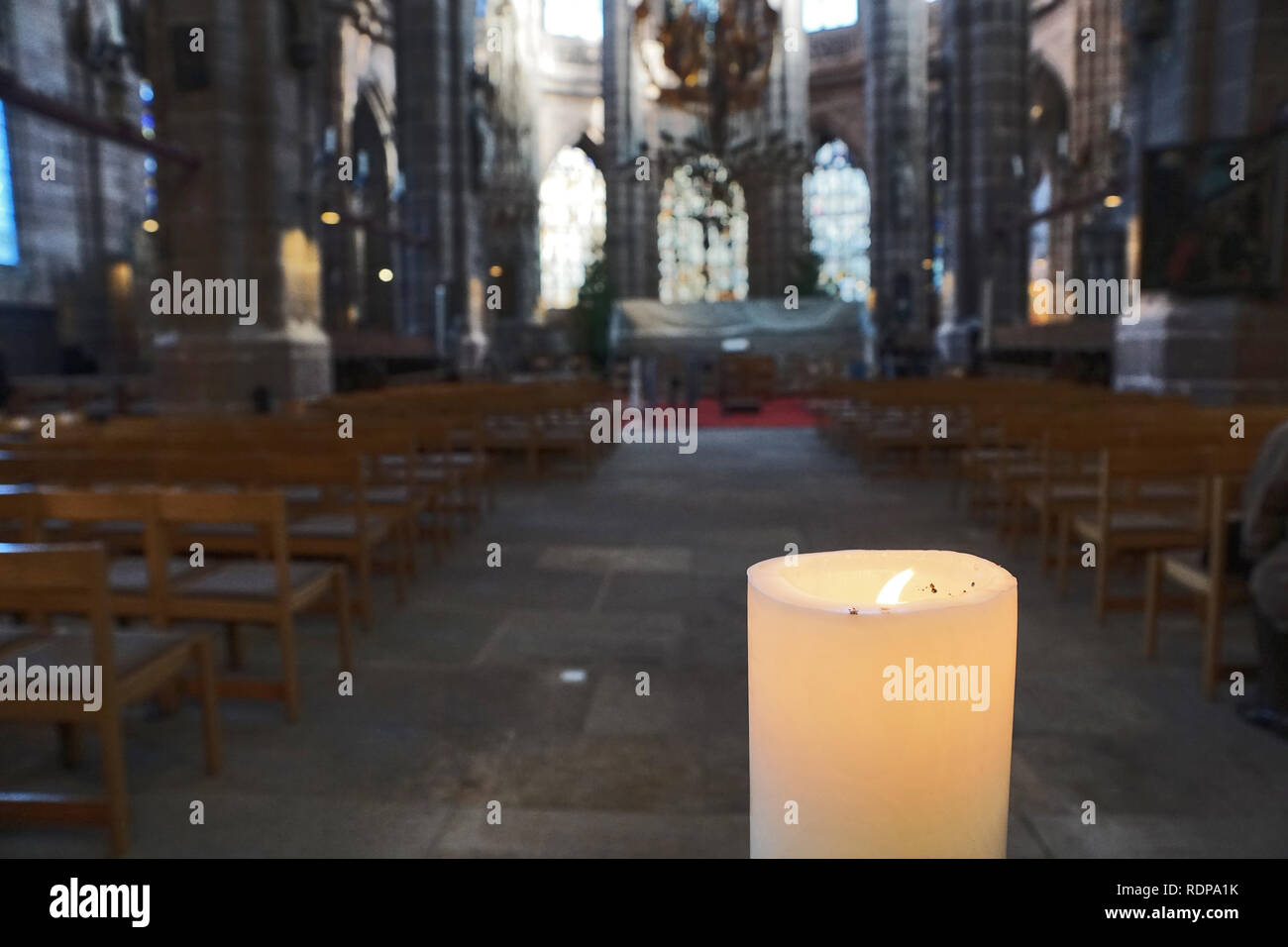 Burning candle in the church - Stock Image