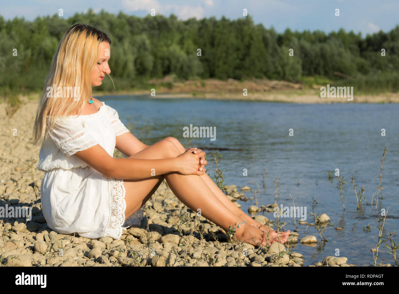 Girl in a short white dress on a gravel bar of the river - Stock Image