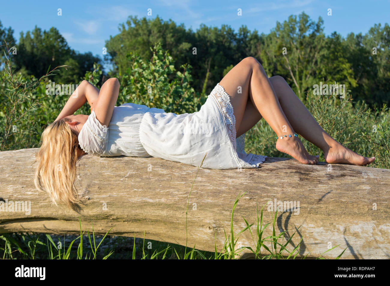 Girl in a short white dress laying on a tree - Stock Image
